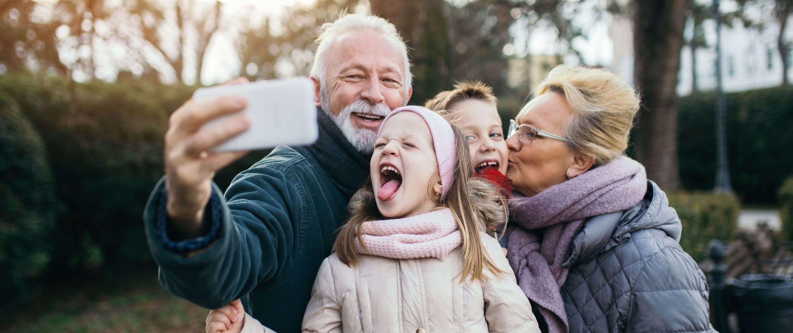Familie mit Opa, Oma und Enkelkindern macht einen Selfie im Garten. Sie lachen und haben Spaß.